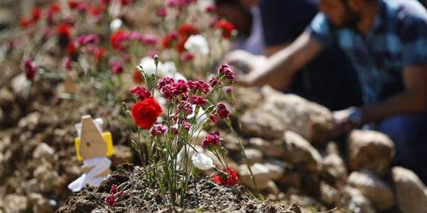 Relatives and friends of victims of the mine accident weep by the graves of their loved ones, following a mass funeral procession in Soma, May 15. AP Photo / Lefteris Pitarakis